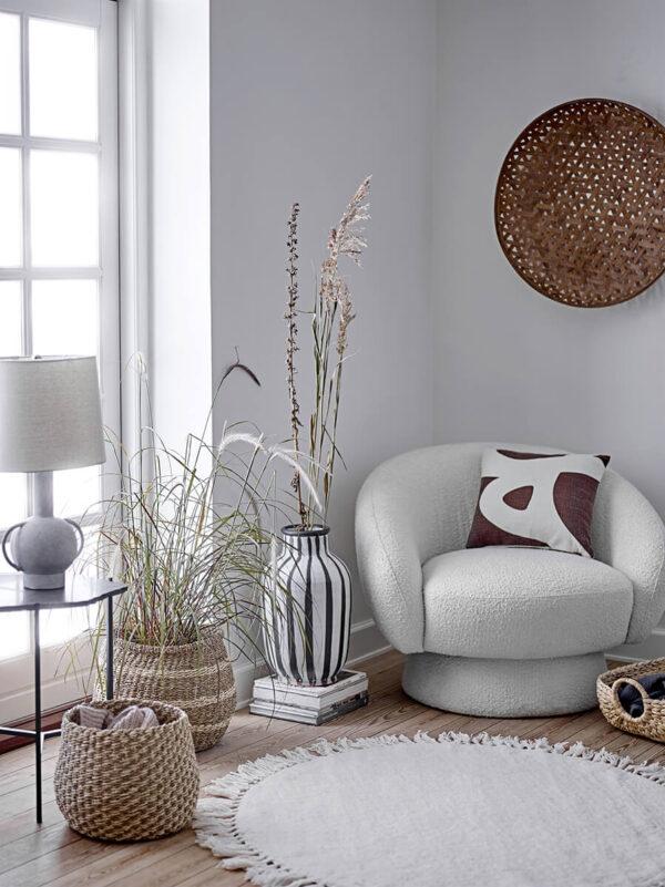 Fehér skandináv pihenő fotel, szürle terrakotta asztali lámpa, bézs gyapjú szőnyeg